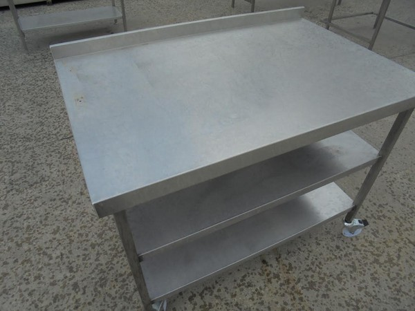 Stainless steel table.  2 Shelves. Upstand. On castors.