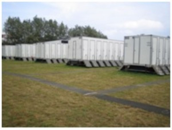 tow-able trailer that has a toilet pan and a sink inside each of the cubicles