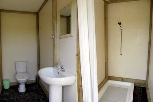 Toilet and Shower Block: 2 Toilets, 2 Showers with Gas Powered Boilers: Adjoining Log Cabin + Sink