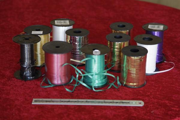 Bobbins of metallic ribbon tether lines