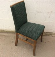 Wooden dining chairs with green seat pads.