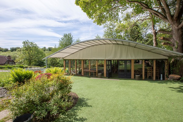 Curved roof framed marquee with glass sides